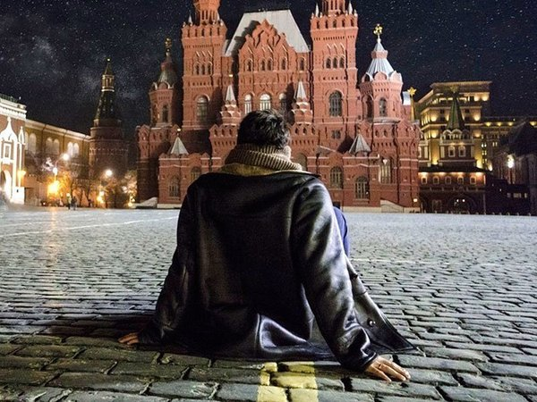 Человек сидит на брусчатке, на Красной площади